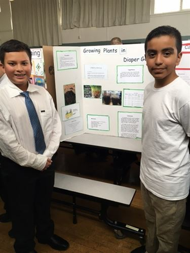 Two boys presenting their science fair project board.